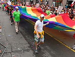 Participants of Gay and lesbian Pride parade carrying large Gay pride flag. Toronto Ontario Canada 2009.