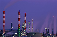 Petroleum refinery chimneys at dusk, France.