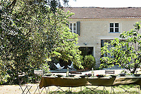 Three antique folding tables have been covered with a large cloth and set for lunch in the garden of a restored farmhouse of a vineyard in Provence