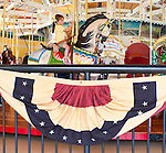 Young girl riding carousel horse, as mother stands next to her, at historic Nunley's Carousel Centennial Celebration on Saturday, June 9, 2012, at Museum Row, Garden City, Long Island, New York, USA. The carousel and grounds were decorated in style of 1912 when carousel debuted, so patiotic banner was red, faded off-white, and blue.