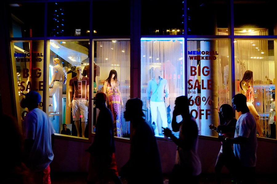 MIAMI BEACH - MAY 25: People walking in front of a storefront during the Urban Beach Weekend, on May 25, 2013 in Miami Beach. This is the largest Urban Festival in the World, that caters towards the Hip Hop Generation. Over 300.000 participants make the annual trek to South Beach for 4 days full of fun, food, festivities, entertainment, music, and more.