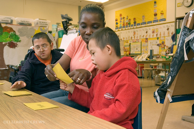 Oakland CA Developmentally disabled primary school students playing word game with aide in special education classroom  MR