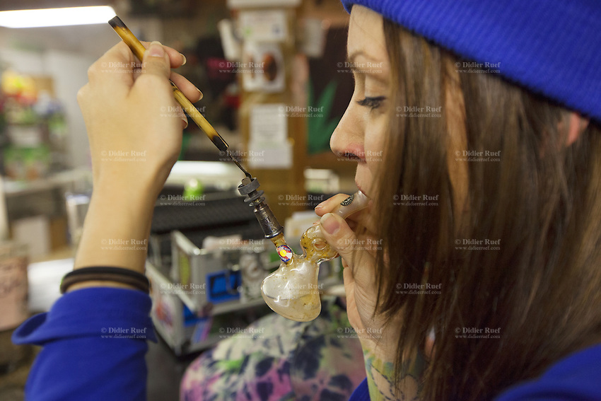 USA. Colorado state. Denver. Dabbing in iBAKE Denver, the first private membership head-shop that people can smoke marijuana in. Anna is dabbing which is a slang term used to describe taking single dose hash hits of concentrates that are referred to as oil, erl, earwax, wax, budder, BHO or shatter using pipes and bongs that are made specifically for smoking these cannabis extracts. The pieces are designed to have a skillet or nail that made from glass, quartz or titanium that is heated with a handheld torch, the user then 'dabs' a small of the extract onto the hot nail causing the concentrate to flash into a vapor that you inhale. Dabbing is the street name for use concentrated butane hash oil, which has THC concentrations as high as 75% (allegedly reaching the 90+ range in some cases) compared with typical pot concentration of about 10 to 15 percent. Depending on the concentrate one long, hard hit can feel as having five blunts at once. The result is a rapid and very strong high. Cannabis, commonly known as marijuana, is a preparation of the Cannabis plant intended for use as a psychoactive drug and as medicine. Pharmacologically, the principal psychoactive constituent of cannabis is tetrahydrocannabinol (THC); it is one of 483 known compounds in the plant, including at least 84 other cannabinoids, such as cannabidiol (CBD), cannabinol (CBN), tetrahydrocannabivarin (THCV), and cannabigerol (CBG). 18.12.2014 © 2014 Didier Ruef