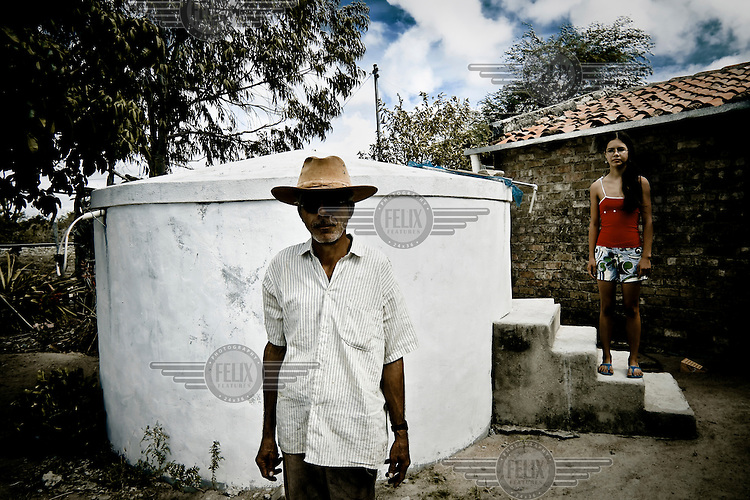 A man and his daughter stand next to a cistern which collects water from a newly installed drain pipe system.