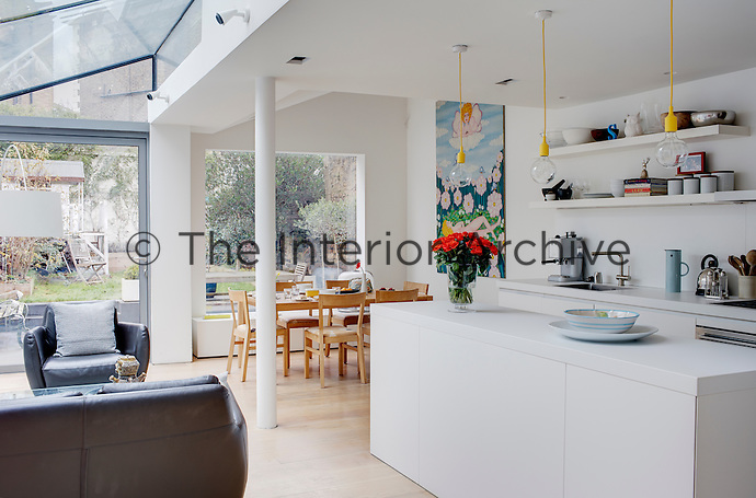 Informal lounge and dining areas furnish a glass-roofed extension fitted out with a Bulthaup kitchen