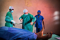 Ophthalmologist Doctor Richard Hardi and his team dress in their medical scrubs prior to surgery in a room, in the remote village of Pania, that they have transformed into an operating theatre. <br /> <br /> From his base in Mbuji Mayi Hungarian ophthalmologist Friar Richard Hardi and his team travelled deep into the Congolese rainforest, by 4x4 and canoe, to treat people in isolated communities most of whom have never seen an ophthalmologist. At a small village called Pania they established a temporary field hospital and over the next three days made hundreds of consultations. Although both conditions are preventable, many of the patients they saw had Glaucoma or River Blindness (onchocerciasis) that had permanently damaged their eyesight. However, patients with cataracts, a clouding of the eye's lens, who were suitable for treatment were booked for an operation. For two days the team carried out the ten minute procedure on one patient after another. The surgery involves making a 2.2mm incision into the remove the damaged lens that is then replaced by an artificial one. Doctor Hardi is one of the few people willing to make such a journey but is inspired to do so by his faith and, as he says: 'Here I feel that I can really make a difference in people's lives'. /Felix Features