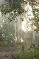 Viriunaveteri, Venezuela. Yanomami boy in early morning light under palm trees..The village of Viriunaveteri consists of 15 huts around a muddy square. It's situated in the Venezuelan Amazone several days by boat from the nearest town. This community on the banks of the Casiquiare is one of the few Yanomami villages that actually has some contact with the outside world. Most other tribes live deeper in the jungle.