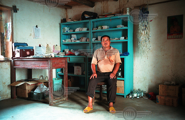 Wu Maolin, a village doctor, still sweating from his work in the rice fields, poses for a picture in his very basic clinic near Yongle. Mr. Wu has worked as a barefoot doctor serving the surrounding mountain areas for 35 years, he has seen over 8,000 patients and has delivered over 200 babies in his career as a medical professional.