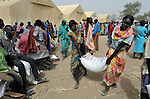 Women carry a bag of sorghum during a food distribution by the United Nations World Food Program in Agok, a town in the contested Abyei region where tens of thousands of people fled in 2011 after an attack by soldiers and militias from the northern Republic of Sudan on most parts of Abyei. Although the 2005 Comprehensive Peace Agreement called for residents of Abyei--which sits on the border between Sudan and South Sudan--to hold a referendum on whether they wanted to align with the north or the newly independent South Sudan, the government in Khartoum and northern-backed Misseriya nomads, excluded from voting as they only live part of the year in Abyei, blocked the vote and attacked the majority Dinka Ngok population. The African Union has proposed a new peace plan, including a referendum to be held in October 2013, but it has been rejected by the Misseriya and Khartoum. The Catholic parish of Abyei, with support from Caritas South Sudan and other international church partners, has maintained its pastoral presence among the displaced and assisted them with food, shelter, and other relief supplies.