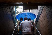 Travelers exit the West 23rd Street subway station in New York on a rainy Sunday, July 29, 2012. (© Richard B. Levine)