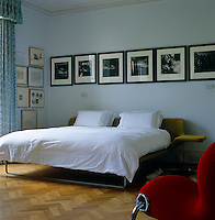 The bedroom is furnished with a contemporary bed and chair and has a series of black and white photographs displayed above the bed