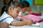 """In the capital of the Philippines, a girl who lives in the Manila North Cemetery draws during a class at the nearby Santa Mesa Heights United Methodist Church. Hundreds of poor families live in the cemetery, inside and between the tombs and mausoleums of the city's wealthy. They are often discriminated against, and many of their children don't go to school because they're too hungry to study and they're often called """"vampires"""" by their classmates. With support from United Methodist Women, KKFI provides classroom education and meals to kids from the cemetery at this church."""