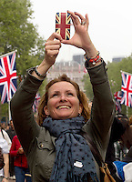 Anne Smith from Perth Scotland holds her phone to take a picture down the mall after Princess Kate and Prince William drive to the Buckingham Palace. .Picture: Maurice McDonald/Universal News And Sport (Europe).29 April 2011..
