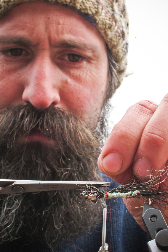 A fly fisherman ties a fly streamside using his own beard hair and a ruffed grouse feather found while steelhead fishing in Michigan.
