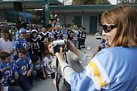 Silver Gate Elementary Principal Sandy McClure videotapes students dressed in San Diego Chargers regalia for a rally on campus in advance of this weekends playoff game, Friday January 11 2008.