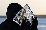A man holds a large clear chunk of ice in front of his face.