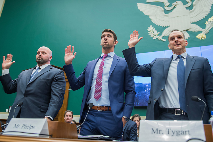 UNITED STATES - FEBRUARY 28: From left, Olympic gold medalists Adam Nelson and Michael Phelps, and Travis Tygart, CEO of the U.S. Anti-Doping Agency, are sworn in during a House Energy and Commerce Subcommittee on Oversight and Investigations hearing in Rayburn Building on ways to strengthen the international anti-doping system, February 28, 2017. Phelps is a swimmer and Nelson a shot putter. (Photo By Tom Williams/CQ Roll Call)