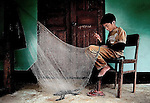 A boy mending his fishing net to use in the Mekong river in northern Laos.