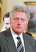 United States President Bill Clinton listens to a reporter's question during a photo op in the Oval Office of the White House in Washington, DC on 30 November, 1999.  The President was announcing a proposed new rule that will allow the states to use their unemployment compensation systems to help offer paid leave to new parents.<br /> Credit: Ron Sachs / CNP
