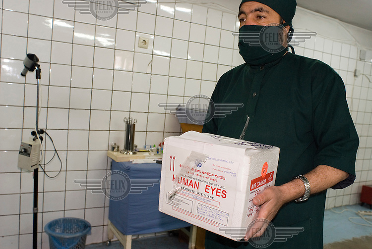 A doctor at Kabul's University Eye Hospital (UEH), on Kabul University campus, transports three newly arrived corneas to the operation room. The 40 bed UEH treats more than 40,000 patients and performs 4,000 sight-saving operations a year.....