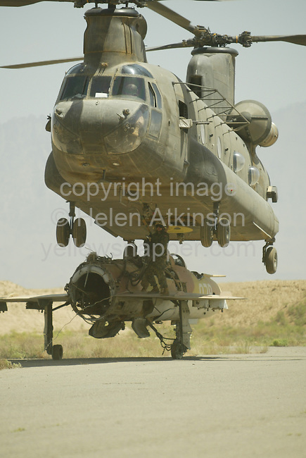 US CHINOOK MOVES BROKEN MIG FROM RUNWAY FOR TARGET PRACTISE, AT BAGRAM AIRBASE, AFGHANISTAN...PICTURE: HELEN ATKINSON