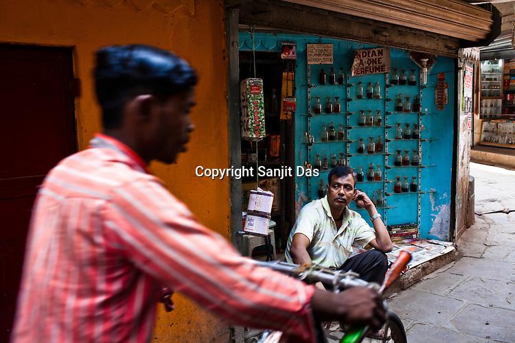 A cyclist rides past an Itr (indian perfume) vendor in the ancient city of Varanasi in Uttar Pradesh, India. Photograph: Sanjit Das/Panos