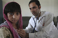 Doctor examining a girl victim of floods in Pakistan