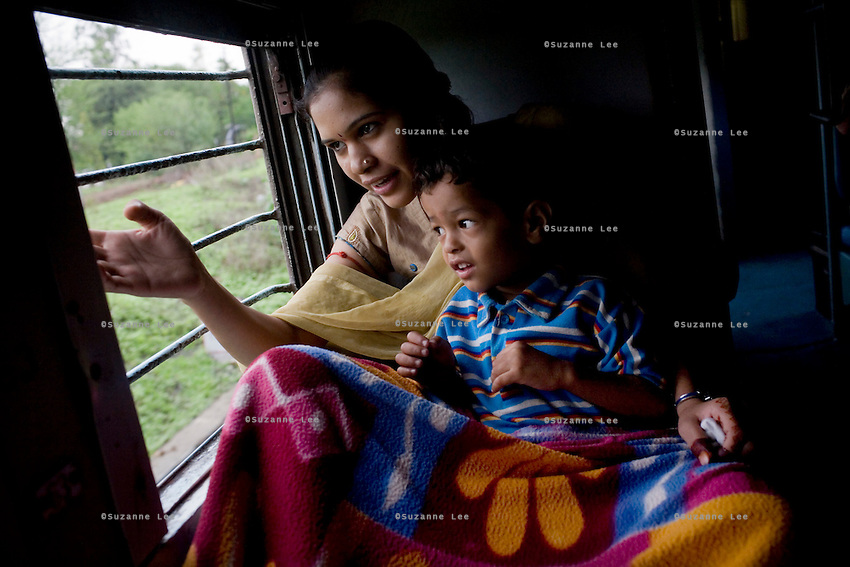 Nisha Goswamy aged 18, and her nephew Ronil Goswami aged 3, look out the window at the greenery of Madhya Pradesh after rain as they pass from Itarsi Junction to Nagpur stn.. They are travelling in a group of 24 people from Bhopal to Kanyakumari for a short holiday and a pilgrimage to 2 temples...Train passengers on the Himsagar Express 6318 going from Jammu Tawi station to Kanyakumari on 8th July 2009.. .6318 / Himsagar Express, India's longest single train journey, spanning 3720 kms, going from the mountains (Hima) to the seas (Sagar), from Jammu and Kashmir state of the Indian Himalayas to Kanyakumari, which is the southern most tip of India...Photo by Suzanne Lee / for The National