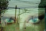 Eyes of advertising in a shop window (of French cosmetics brand Lancome) and reflection of cables and surveillance cameras on the street...From China [sur]real © Mark Henley..