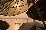 Umbrellas on ghats (riverfront) overlooking the Ganges, India