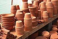 Pots &amp; containers in piles on potting shed bench, new terracotta clay pots