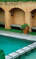 This Spanish style walled garden is dominated by an azure blue swimming pool
