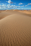 Sahara desert sand dunes with cloudy blue sky at Erg Lihoudi, M'hamid, Morocco