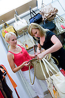 Two Women looking and comparing different handbags in shop. Fashion, retail store, shopping. Shoulder bags on shelves.