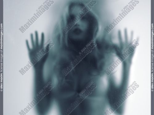 Dramatic expressive concept of a blurred sensual young woman silhouette behind a hazy scratched glass