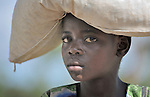 A young woman in Matuli, Malawi, carries grain on her head.