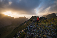 Female hiker watches sunset from the summit of Markan (602m), Moskensøy, Lofoten Islands, Norway