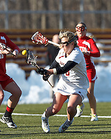 A tripped Boston College attacker Covie Stanwick (8) shoots the ball, on her way to the ground..Boston College (white) defeated Boston University (red), 12-9, on the Newton Campus Lacrosse Field at Boston College, on March 20, 2013.
