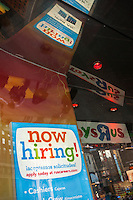 A sign in the window of Toys R Us in Times square in New York advises potential job applicants of the seasonal employment opportunities available, seen on Friday, October 9, 2015. Toys R Us recently announced that they will hire 40,000 seasonal workers, down from 45,000 last year, but will offer more hours to those hired. (© Richard B. Levine)