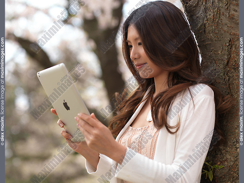 Young Asian woman with iPad in a park under a cherry tree