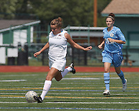 Boston Aztec midfielder/defender Alex Bengston (9) brings the ball forward.  In a Women's Premier Soccer League (WPSL) match, Boston Aztec (white) defeated Seacoast United Mariners (blue), 2-1, at North Reading High School Stadium on Arthur J. Kenney Athletic Field on on June 23, 2013. Due to injuries through the season, Seacoast United Mariners could only field 10 players.