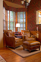 Cozy reading nook with leather reading chairs and paisley wallcovering