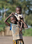 A girl carries her younger sibling in the Makpandu refugee camp in Southern Sudan, 44 km north of Yambio, where more that 4,000 people took refuge in late 2008 when the Lord's Resistance Army attacked their communities inside the Democratic Republic of the Congo. Attacks by the LRA inside Southern Sudan and in the neighboring DRC and Central African Republic have displaced tens of thousands of people, and many worry the attacks will increase as the government in Khartoum uses the LRA to destabilize Southern Sudan, where people are scheduled to vote on independence in January 2011. Catholic pastoral workers have accompanied the people of this camp from the beginning. NOTE: In July 2011 Southern Sudan became the independent country of South Sudan.
