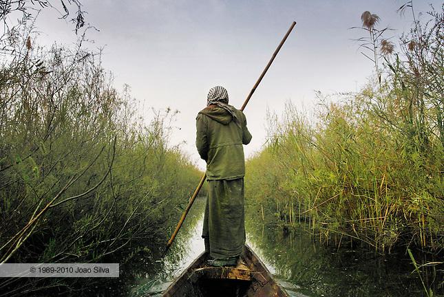 Iraq: Kurmashia Marsh: February 18, 2004: A Marsh Arab poles his canoe through Kirmashiya Marsh in southern Iraq.