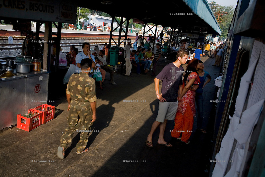 An Indian Army Personnel walks by as passengers check the name list pasted on the train. Dhuri Junction Stn., Punjab on 7th July 2009.. .6318 / Himsagar Express, India's longest single train journey, spanning 3720 kms, going from the mountains (Hima) to the seas (Sagar), from Jammu and Kashmir state of the Indian Himalayas to Kanyakumari, which is the southern most tip of India...Photo by Suzanne Lee / for The National