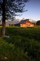 Moulton Barn at sunrise with rainbow on Mormon Row against the Teton Range Mountains in Grand Teton National Park.