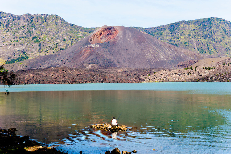Man Fishing infront of Mount Barujari in Segara Anak Lake at the Bottom of Mount Rinjani Crater, Lombok, Indonesia. On arriving at the bottom of Moung Rinjani crater, there were people fishing in Segara Anak Lake. A pretty spectacular setting, with the summits of both Mount Barujani and Mount Rinjani tower above.