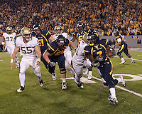 WVU running back Noel Devine (7)  heads upfield as Pitt's Max Gruder (55) closes in. The West Virginia Mountaineers defeated the Pittsburgh  Panthers 19-16 on November27, 2009 at Mountaineer Field at Milan Puskar Stadium, Morgantown, West Virginia.