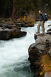 A hiker stands on the edge of the Rogue River as it crashes through a gorge, Rogue River National Forest, Oregon