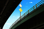Merge Traffic sign on highway bridge from low angle, Bronx, New York City